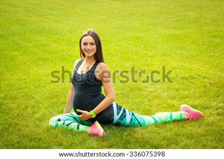The beautiful pregnant woman practices yoga on a lawn - stock photo