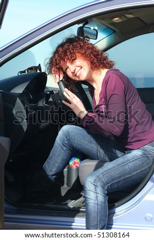 The beautiful red-haired girl smiles in the car