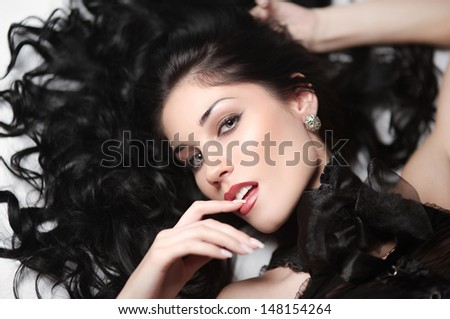 the beautiful sexy strict woman with long black hair.  Fashion model posing at studio. - stock photo