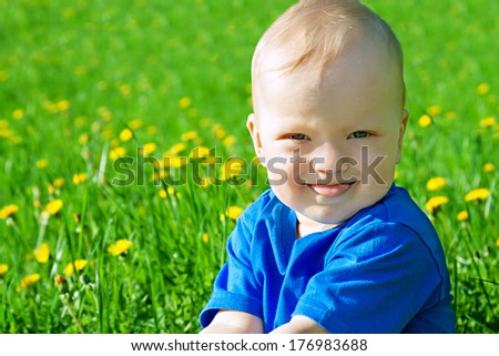 the beautiful small child the boy plays on a green meadow - stock photo