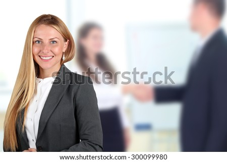 The Beautiful smiling business woman  portrait. handshake between two colleagues behind - stock photo
