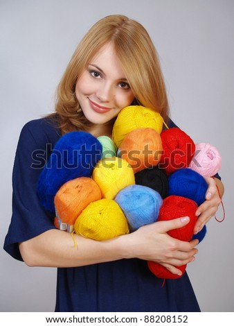 The beautiful smiling girl has control over a lot of a color yarn