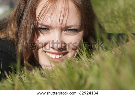 The beautiful smiling girl lies on green grass