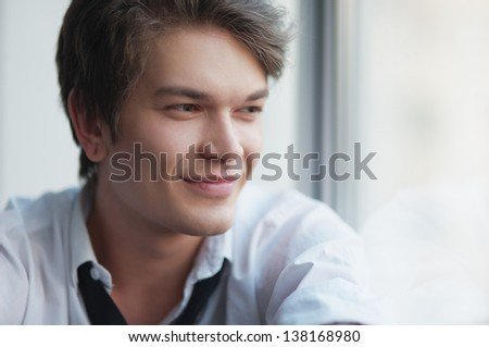 the beautiful smiling young man in a shirt looks out of the window - stock photo