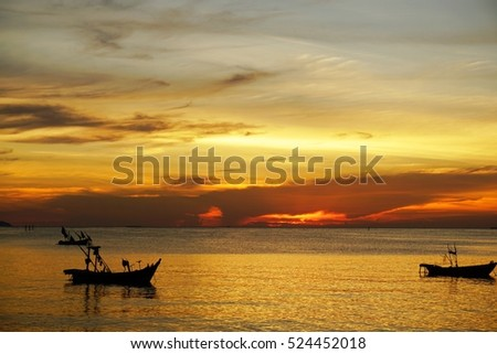 The beautiful sunset sky with the fishing boats on the sea.