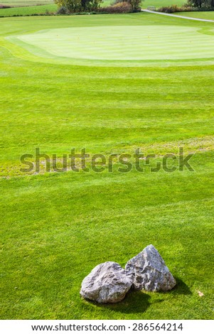 the beautiful vibrant putting green of an Austrian golf course on a sunny day - stock photo