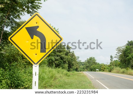 the beautiful winding road sign in yellow background and black arrow - stock photo