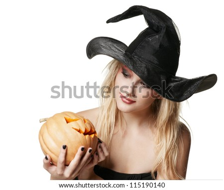 The beautiful witch holds an orange  pumpkin in a black hat - stock photo