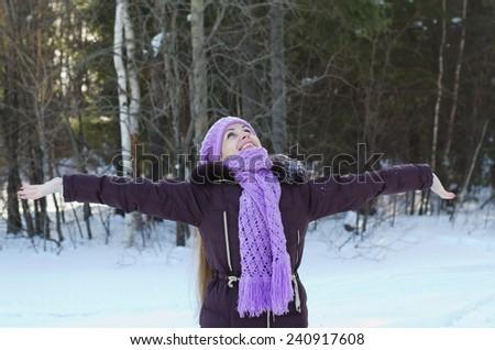 The beautiful woman has fun on walk in winter wood  - stock photo