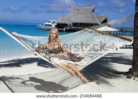 the beautiful woman in a long sundress in a hammock on a sea background - stock photo
