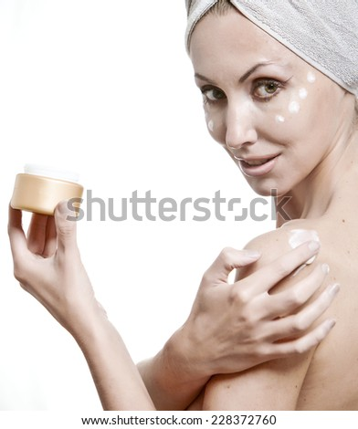 The beautiful woman in a towel puts cream - stock photo