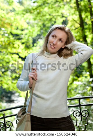 The beautiful woman in a white sweater on the bank of the lake against bright green foliage