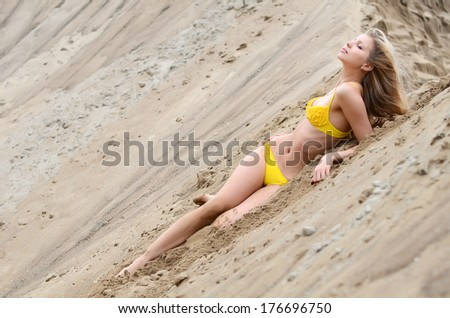 The beautiful woman in bikini on sand - stock photo