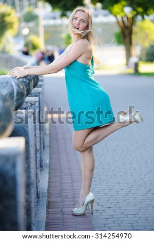 The beautiful woman in elegant blue dress in the summer city