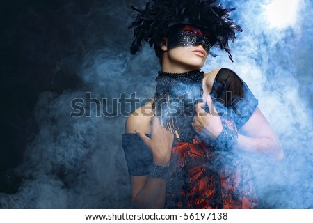 The beautiful woman in feathers and glass stones, in a smoke