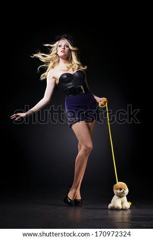 The beautiful woman is posing with toy dog - stock photo