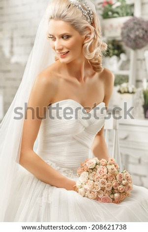 The beautiful  woman posing in a wedding dress - stock photo