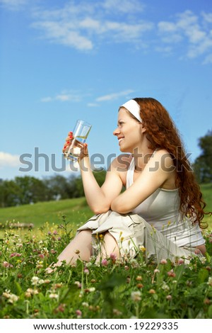 The beautiful woman sits on a lawn and drinks water