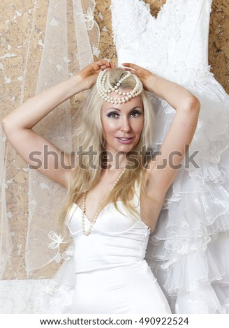 The beautiful woman, the bride, near wedding dress dreams about wedding
