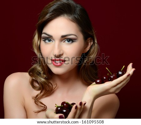 The beautiful woman with a sweet cherry - stock photo
