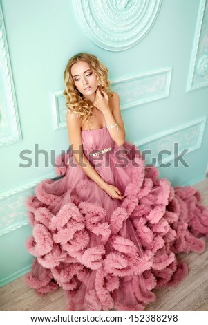 The beautiful woman with blonde, curly hair, tender makeup posing in a wedding dress. - stock photo