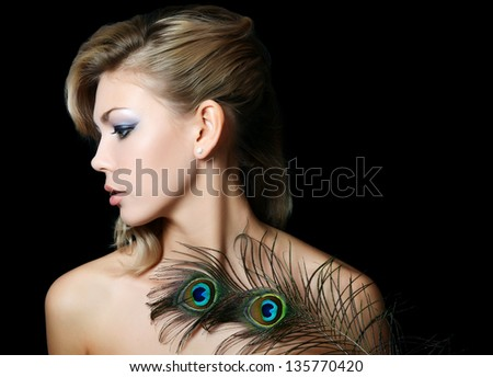 The beautiful woman with feathers of peacock - stock photo
