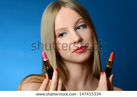 The beautiful woman with lipsticks in hands - stock photo
