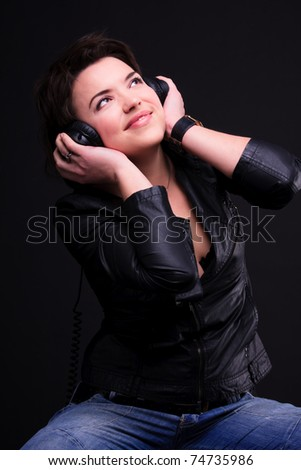 The beautiful young brunette girl in headphones