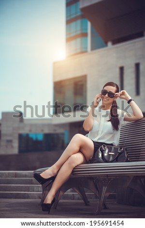 The beautiful young city woman sits on a bench - stock photo