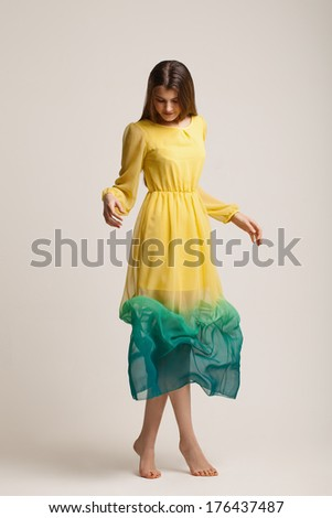 The beautiful young girl in a fashionable dress. Studio portrait.  Isolated