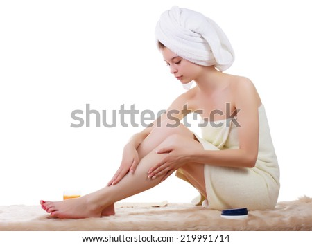 The beautiful young girl in a towel, sitting masses the feet. White background. - stock photo