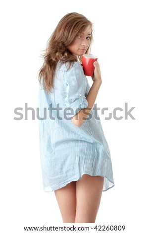 The beautiful young woman drinks morning coffee or tea