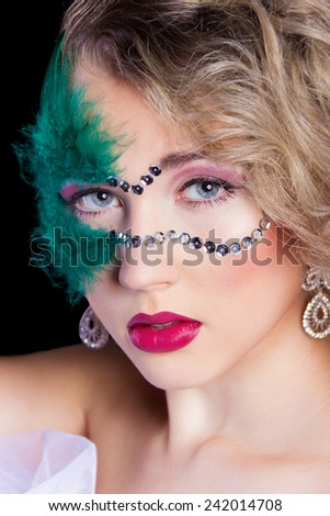 The beautiful young woman in a green mysterious venetian mask a new year carnival, Christmas masquerade, a dance club, secret night party, with beautiful makeup