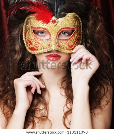The beautiful young woman in a red mysterious  mask - stock photo