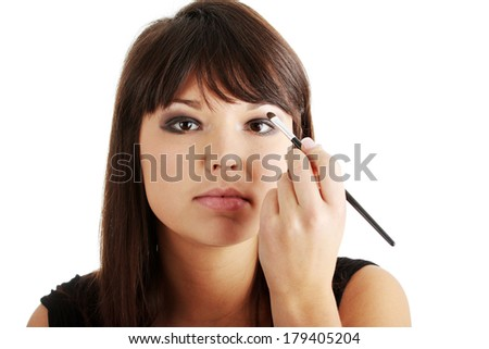 The beautiful young woman in elegant black dress does a make-up, isolated on a white background