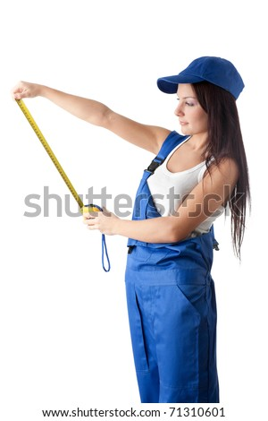 The beautiful young woman in overalls with a measuring tape in hands on a white background.