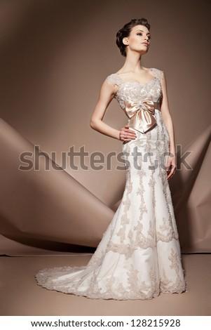 The beautiful young woman posing in a wedding dress - stock photo