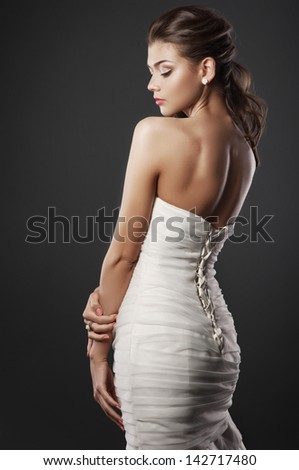 The beautiful young woman posing in a wedding dress on a grey background - stock photo