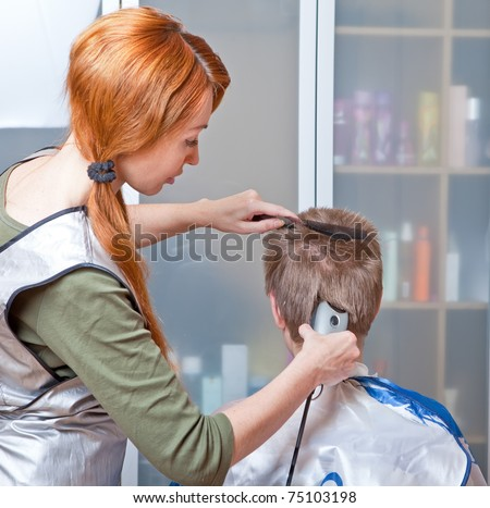 The beautiful young woman the hairdresser does a  hairstyle to the client - young man