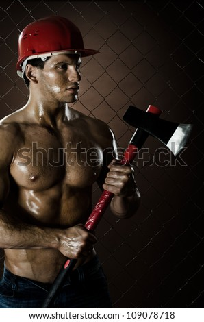 the beauty muscular worker  chopper  man, in  safety helmet  with big  heavy ax  in hands,  on netting fence background - stock photo