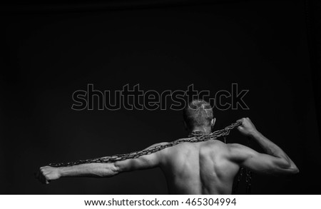 The beauty muscular worker man, with big chain in hands, on  background