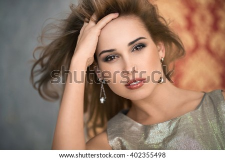 The beauty of a woman. Beautiful young woman touching her skin. Portrait isolated on gray. Healthcare. Perfect Skin. The beauty of the face. - stock photo