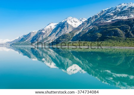 The Beauty of Alaska | Alaska: Mountains reflecting in still water of Glacier Bay. Glacier Bay National Park and Preserve, Alaska, United States - stock photo