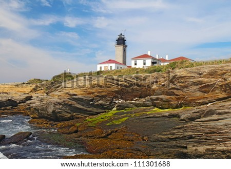 The Beavertail Light lighthouse near Jamestown on Conanicut Island, Rhode Island, viewed from the rocky coast with a bright blue sky and white clouds - stock photo