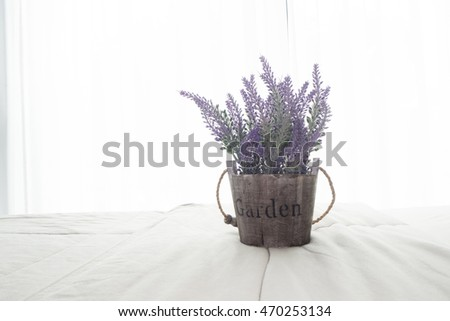 The bed with purple lavender flower and sunlight from glass of windows in bedroom, High key picture style.