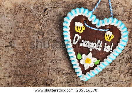 The beer is tapped - original german bavarian Oktoberfest gingerbread heart on real brown tree bark from Germany  - stock photo