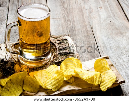 The beer style . Glass of beer on a birch stand and chips on wooden background. - stock photo