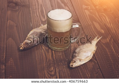 The beer with dried fish on the wood table