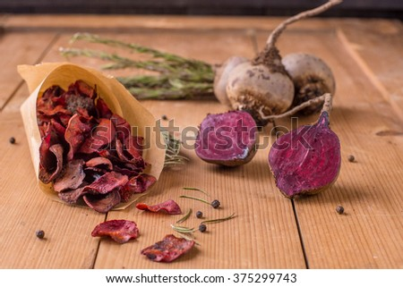 The beet chips with rosemary on a wooden background