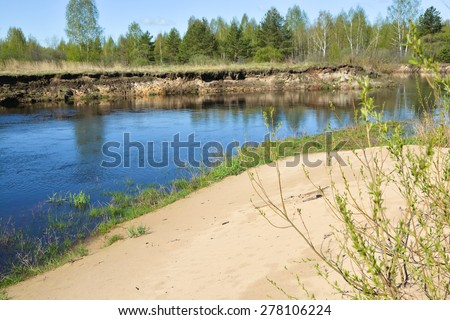 The beginning of may on a protected river. Spring landscape, the river and the first greens in the trees. - stock photo